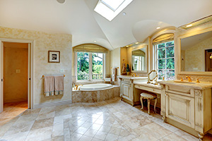 Spacious luxury bathroom with high vaulted ceiling and velux window. View of antique old vanity with cabinets and bath tub with arch window
